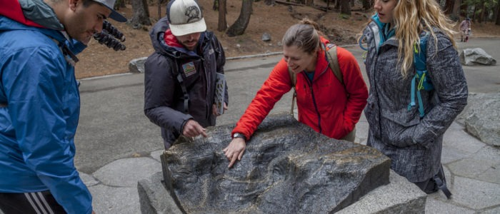 Visitors explore the area around Lower Yosemite Fall, which includes a bronze relief map of the waterfall and surrounding terrain. Photo: Yosemite Conservancy/Keith Walklet.