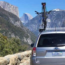 A car with a Yosemite license plate at a turnout on Wawona Road, with Half Dome and El Capitan visible. Photo: Sandra Callan.