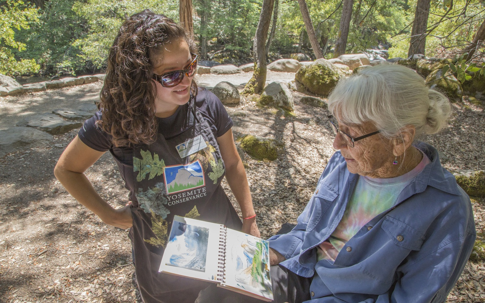 Sylvia Eneriz, one of our 2019 volunteer art instructors, works with a participant during a summer class near Happy Isles.