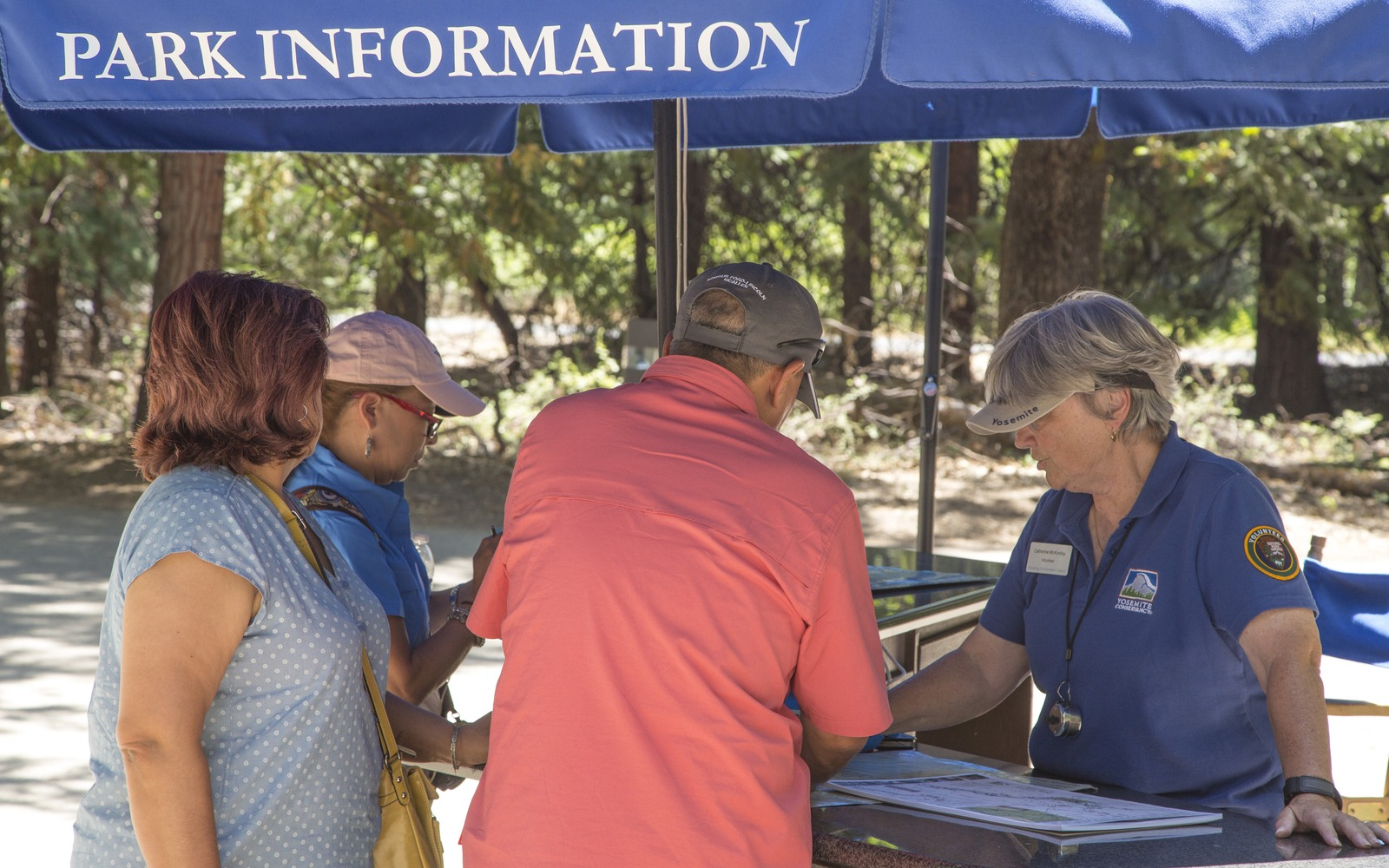 "One of our 2019 visitor information assistants talks to visitors at a blue ""Park Information"" tent near the Yosemite Valley Visitor Center."