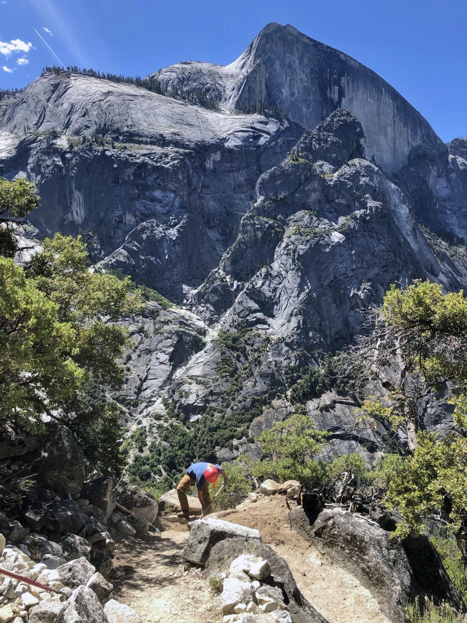Photo of a worker on the Snow Creek Trail in Yosemite, with Half Dome in the background.