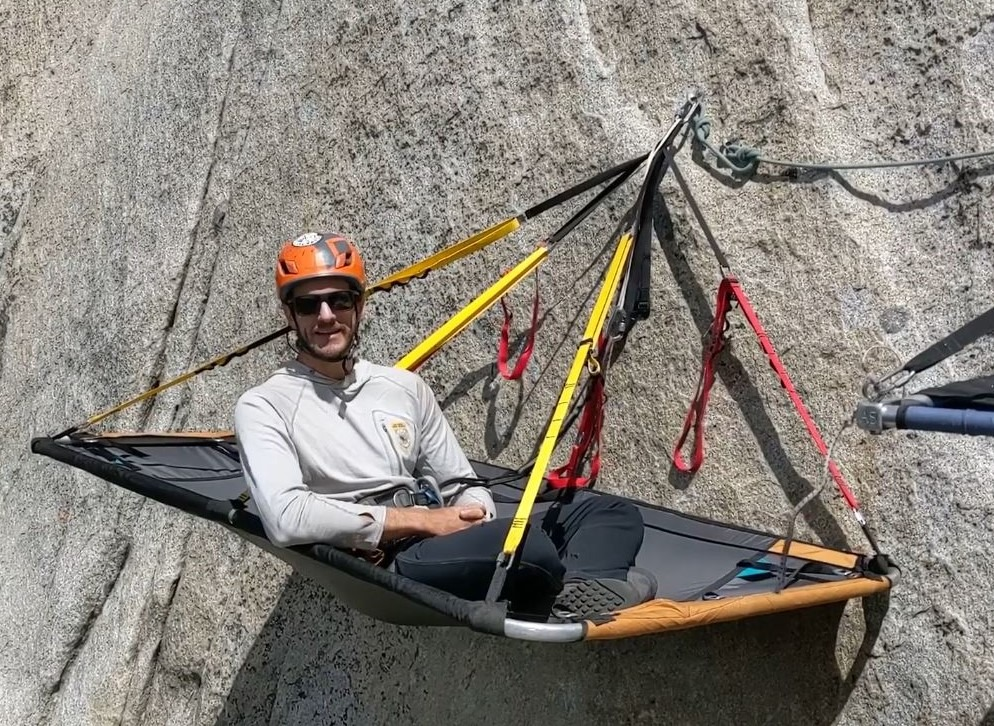 "A Yosemite climbing ranger using a portaledge on a rock wall in the park This is a screenshot from a ""Behind the Scenes"" video that Yosemite National Park posted in June 2020."