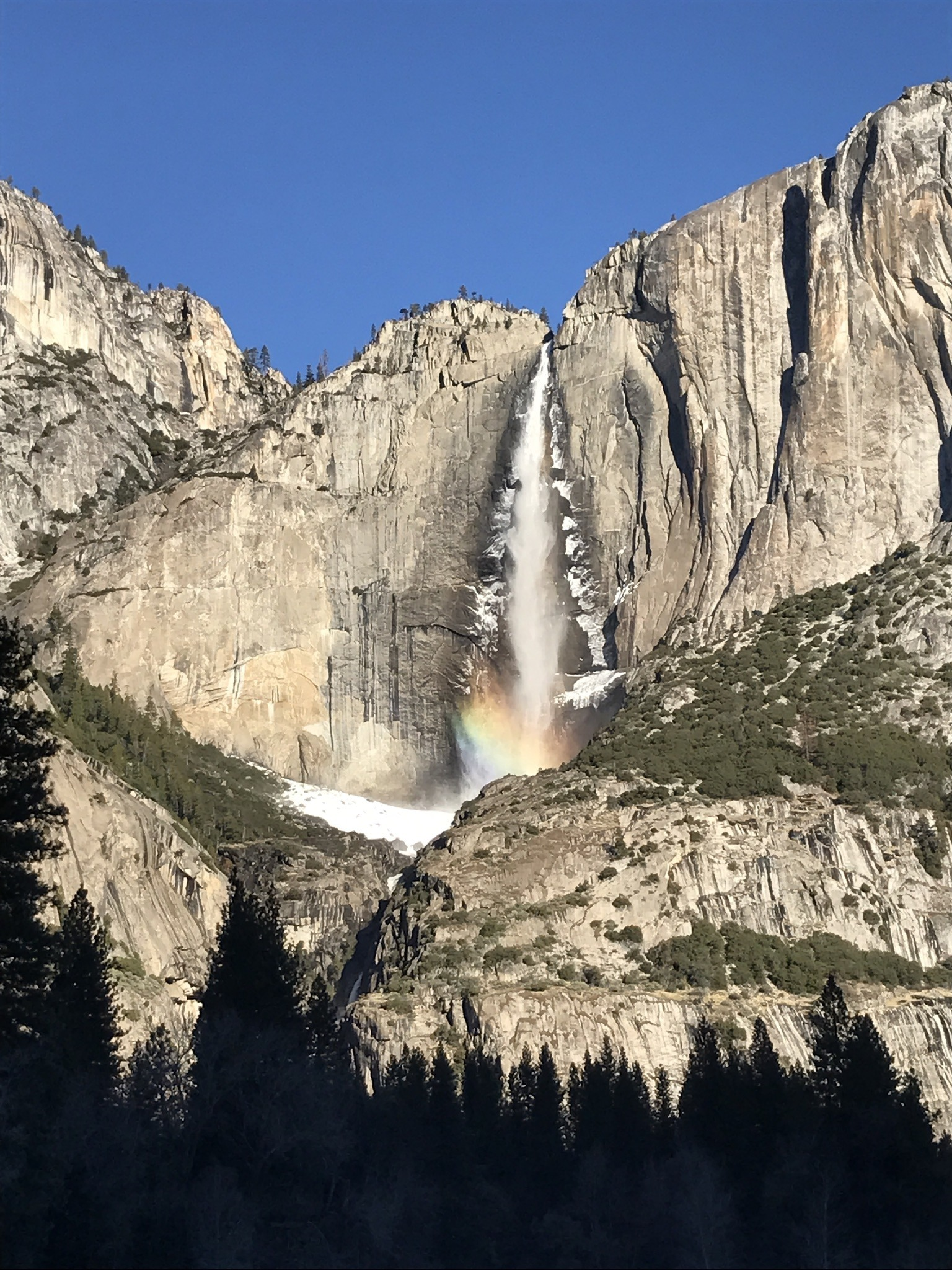 A beauty shot of Yosemite Falls, with a rainbow visible in the mist and snow piled up at the base of the upper fall. Photo: Melissa King.