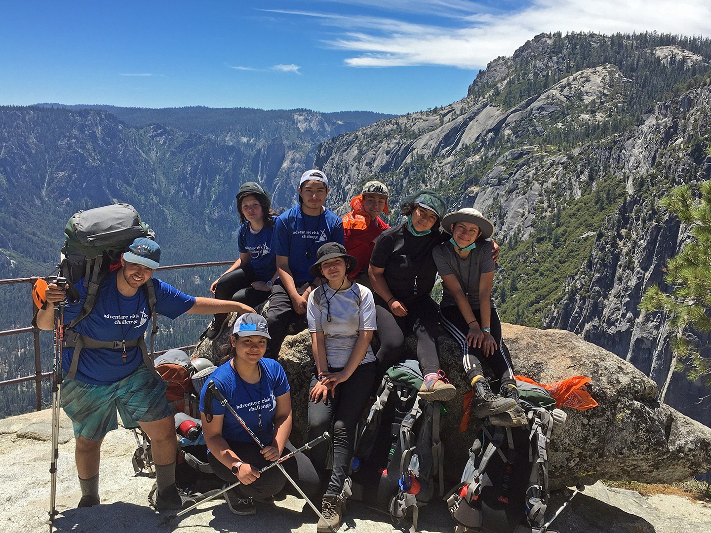 The eight high school students participating in the 2020 Adventure Risk Challenge summer course pose for a group photo at the overlook above Yosemite Falls, with Yosemite Valley stretching out in the background.