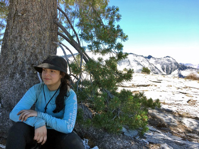 Asucena, a participant in the Adventure Risk Challenge 2020 summer course, sits by a tree in Yosemite's high country.