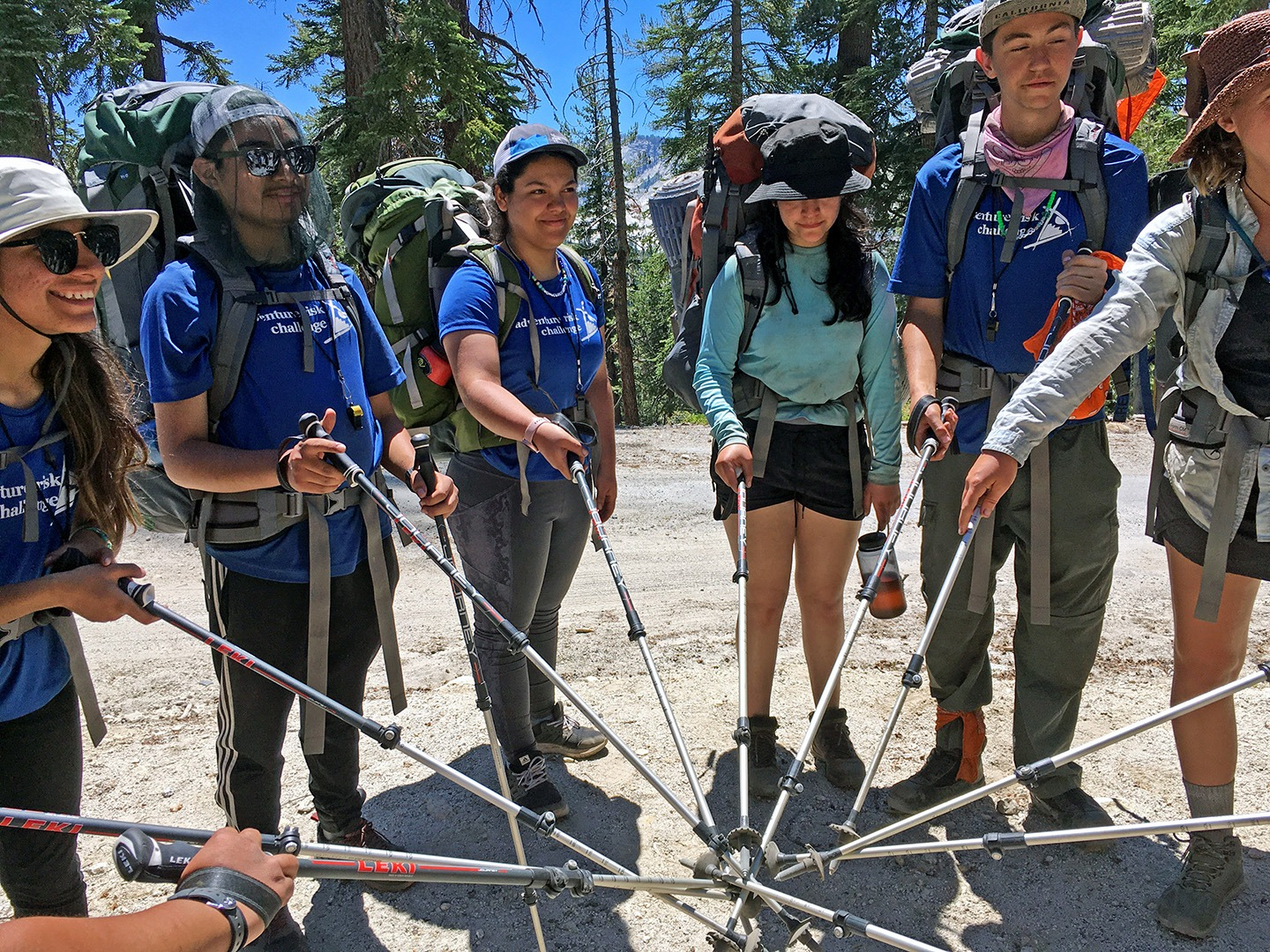 Adventure Risk Challenge students stand in a circle with their hiking poles in the center during a backpacking trip in the Yosemite Wilderness.