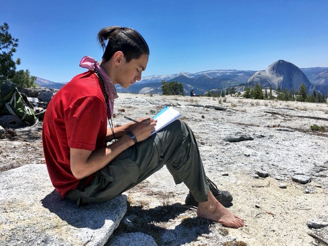 An Adventure Risk Challenge student writes in a journal while sitting on a granite expanse in Yosemite, with Half Dome visible in the distance.