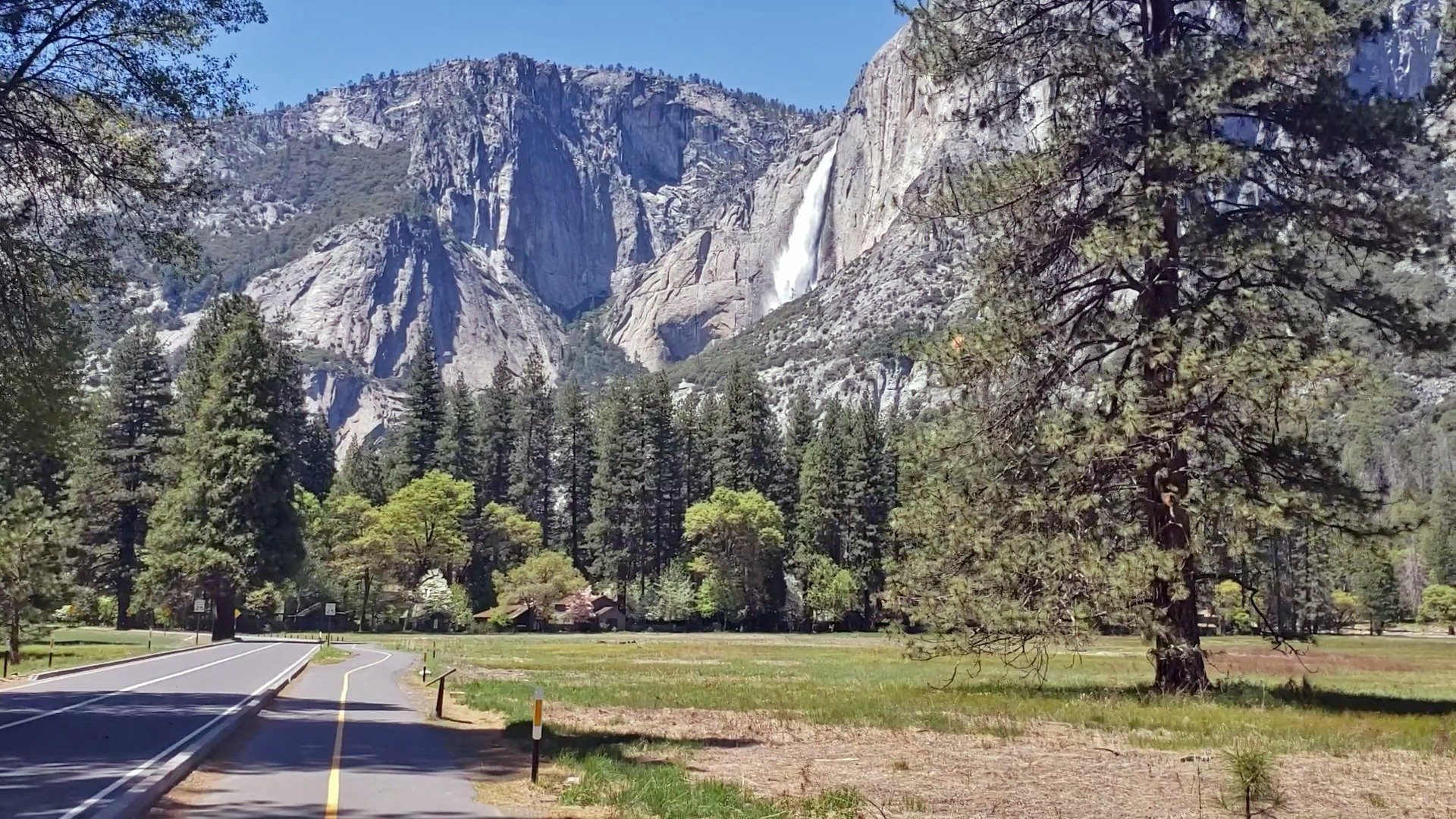 A scenic shot of a empty bike path and road in Yosemite Valley, with Yosemite Falls visible at right. Photo: Cory Goehring