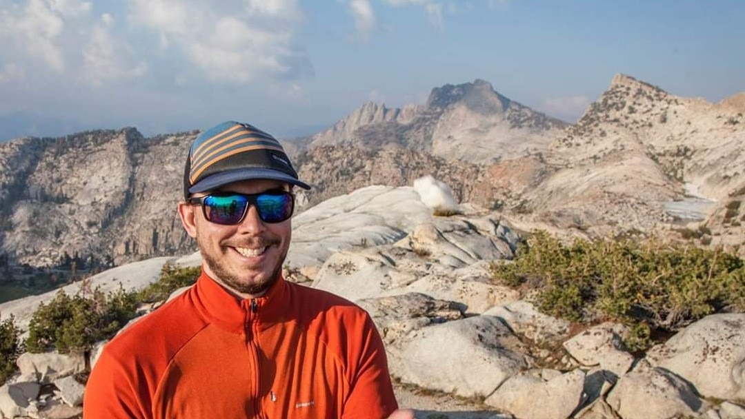 Yosemite Conservancy's lead naturalist, Cory Goehring, smiles on a high country ridge, with mountains in the background.