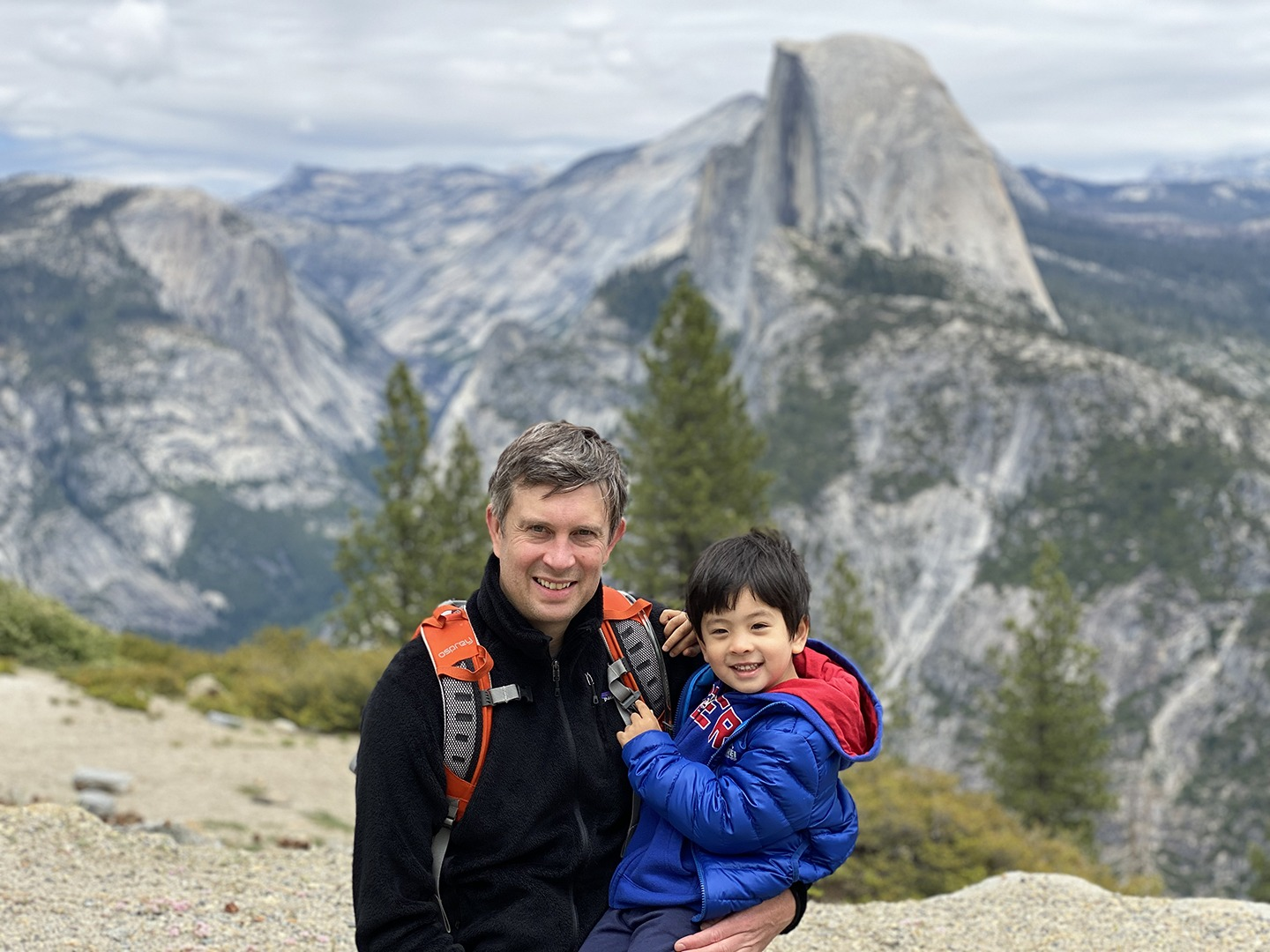 Mike Ashton holds his 4-year-old son, Owen, at Glacier Point. Both smile at the camera, and Half Dome is visible in the background.