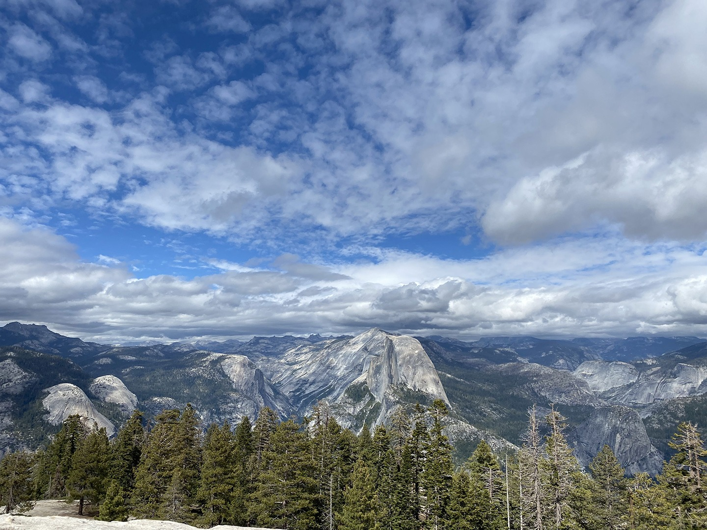 A landscape photo of the view from Sentinel Dome, with Half Dome, Clouds Rest and distant Sierra Nevada peaks visible.