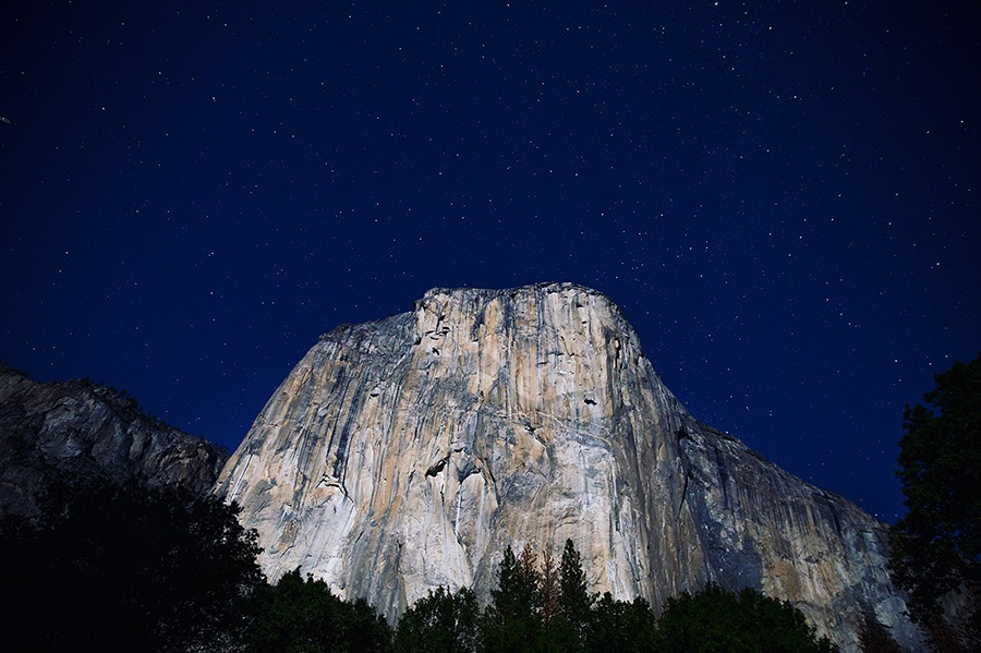 A horizontal landscape shot looking up at El Capitan at night, with stars visible in the dark blue sky above the gleaming granite.