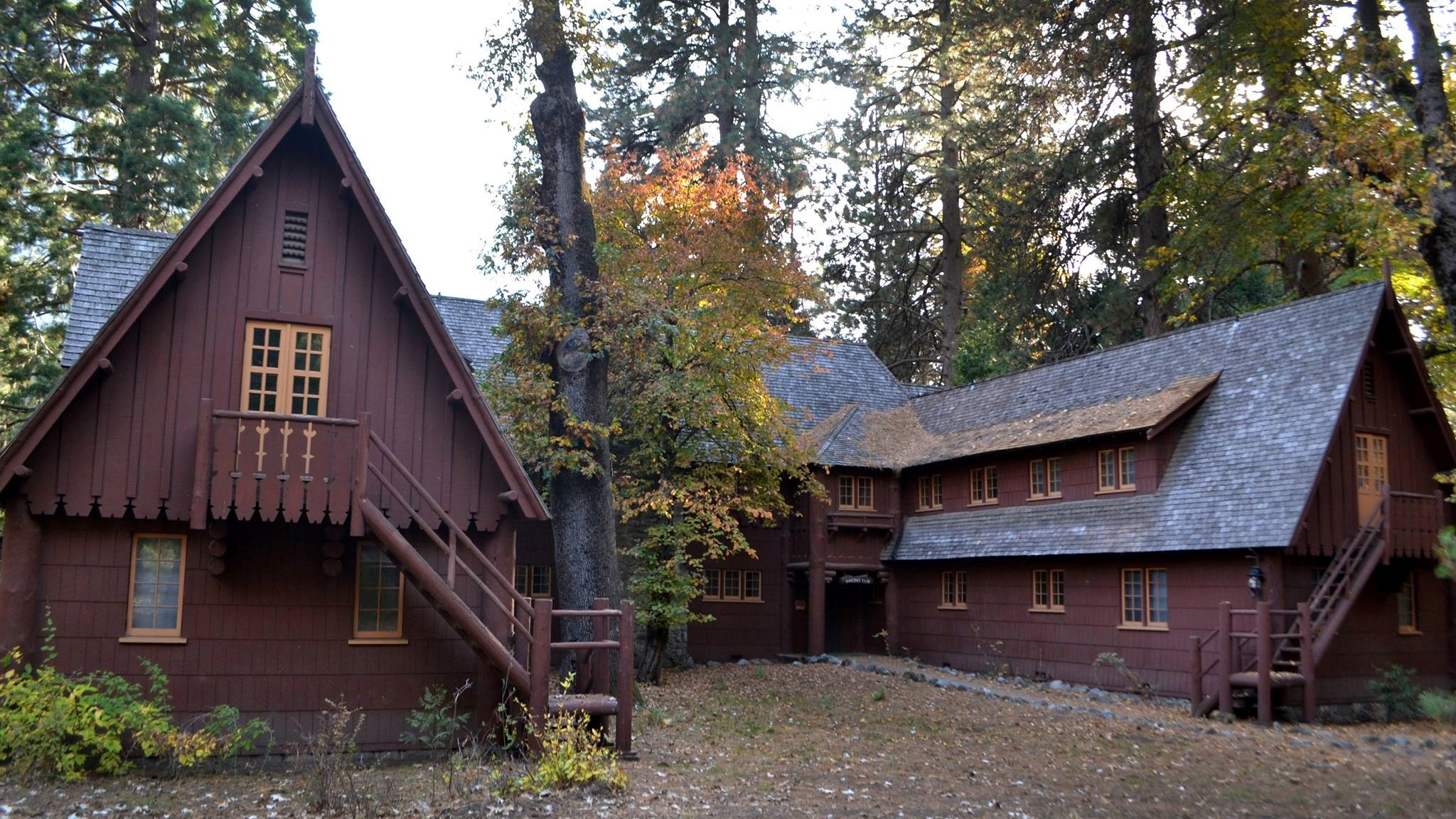 View of the front side of the Rangers' Club in Yosemite Valley, showing high pointed roofs and a courtyard between the building's two wings. Photo: Courtesy of NPS.