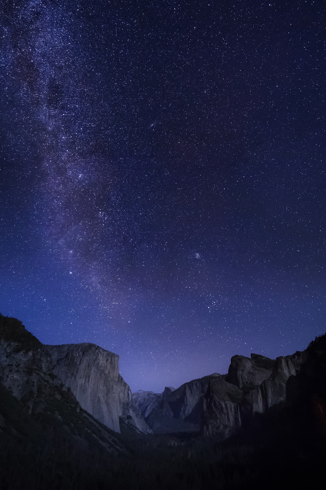 A vertical landscape photo showing Tunnel View under a deep blue and purple night sky, with the Milky Way glittering over El Capitan, Half Dome and Cathedral Rocks.