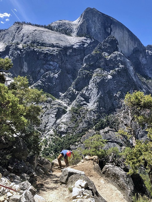 A trail worker wearing a red helmet works on a switchback on the Snow Creek Trail, with Half Dome visible in the background.