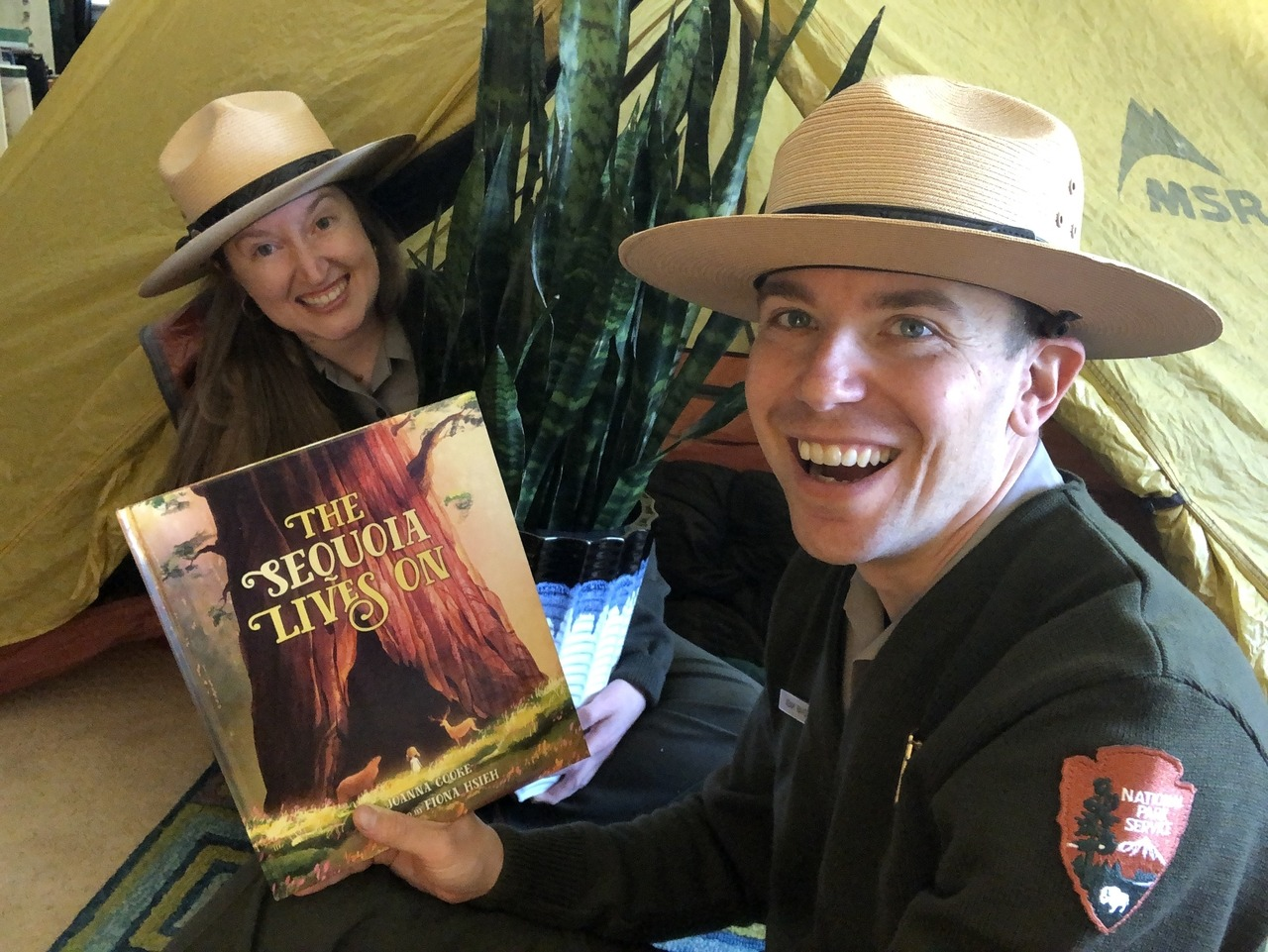 """Two Yosemite rangers in uniform host a live reading from their house. One ranger holds the children's book """"The Sequoia Lives On,"""" while the other peers out from a tent."""