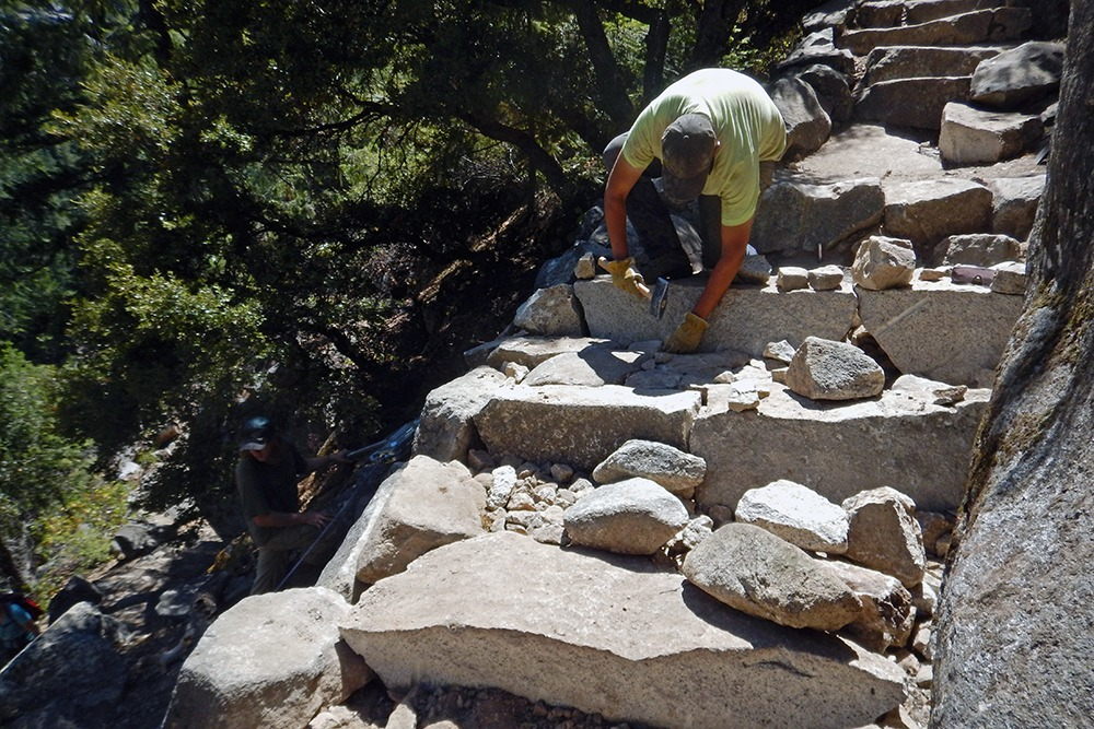 A trail crew worker uses a hammer while working on large stone steps on the John Muir Trail. Photo: Courtesy of NPS.