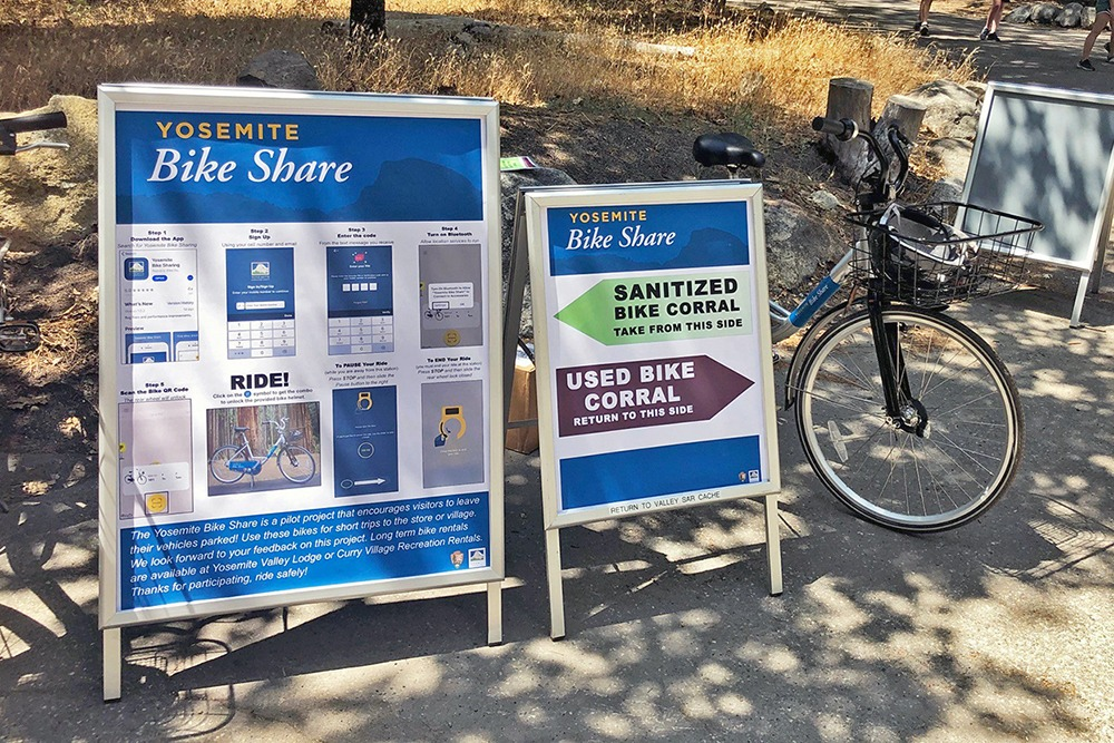 A Yosemite Bike Share station in Yosemite Village, showing signs explaining how to use the service and where to pick up sanitized bikes and drop off used bikes. Photo: Yosemite Conservancy/Schuyler Greenleaf.
