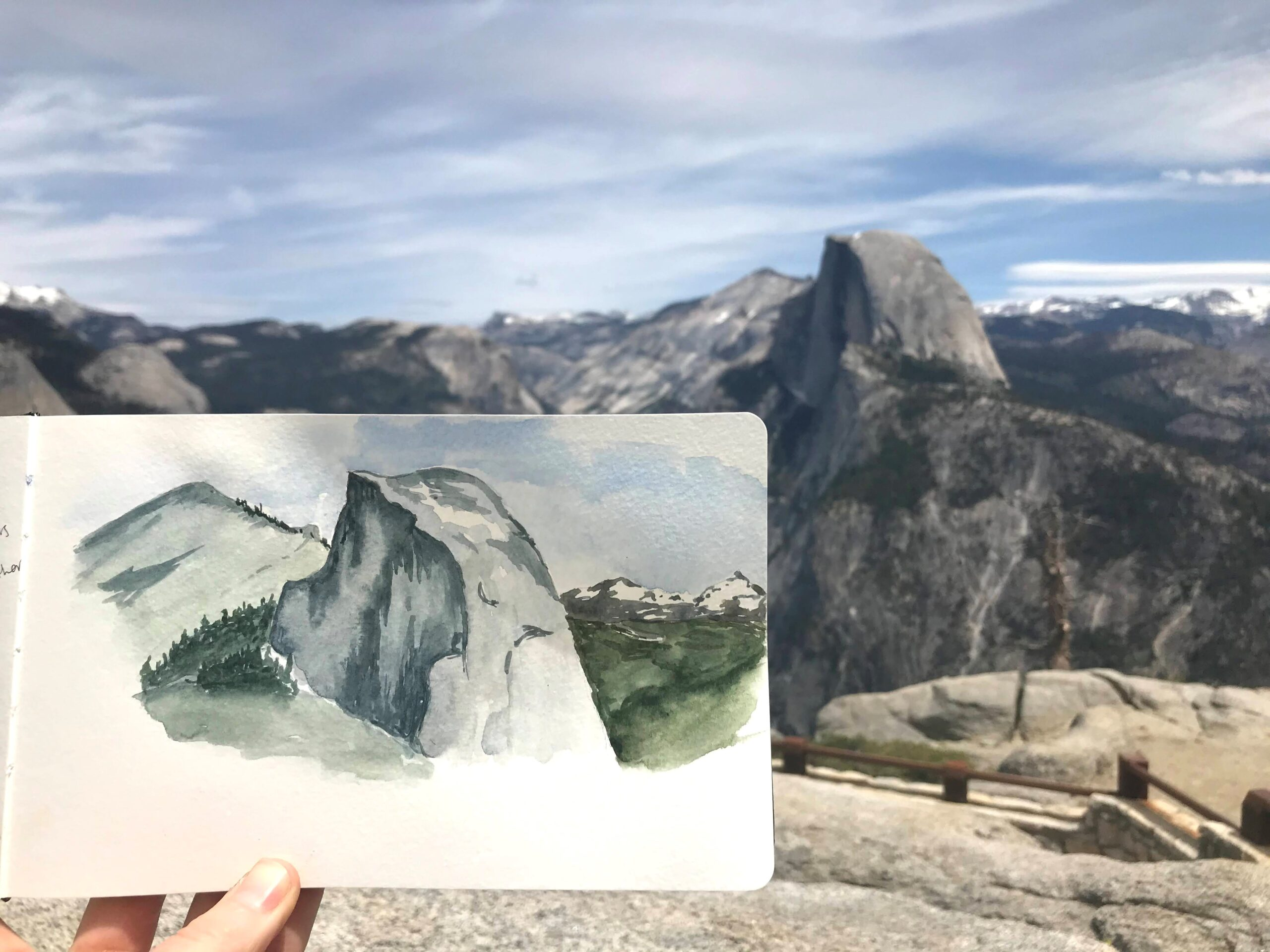 A person's hand holds a watercolor sketch of Half Dome and Clouds Rest, at Glacier Point. Behind the paper, the real-life features and surrounding mountains are visible.