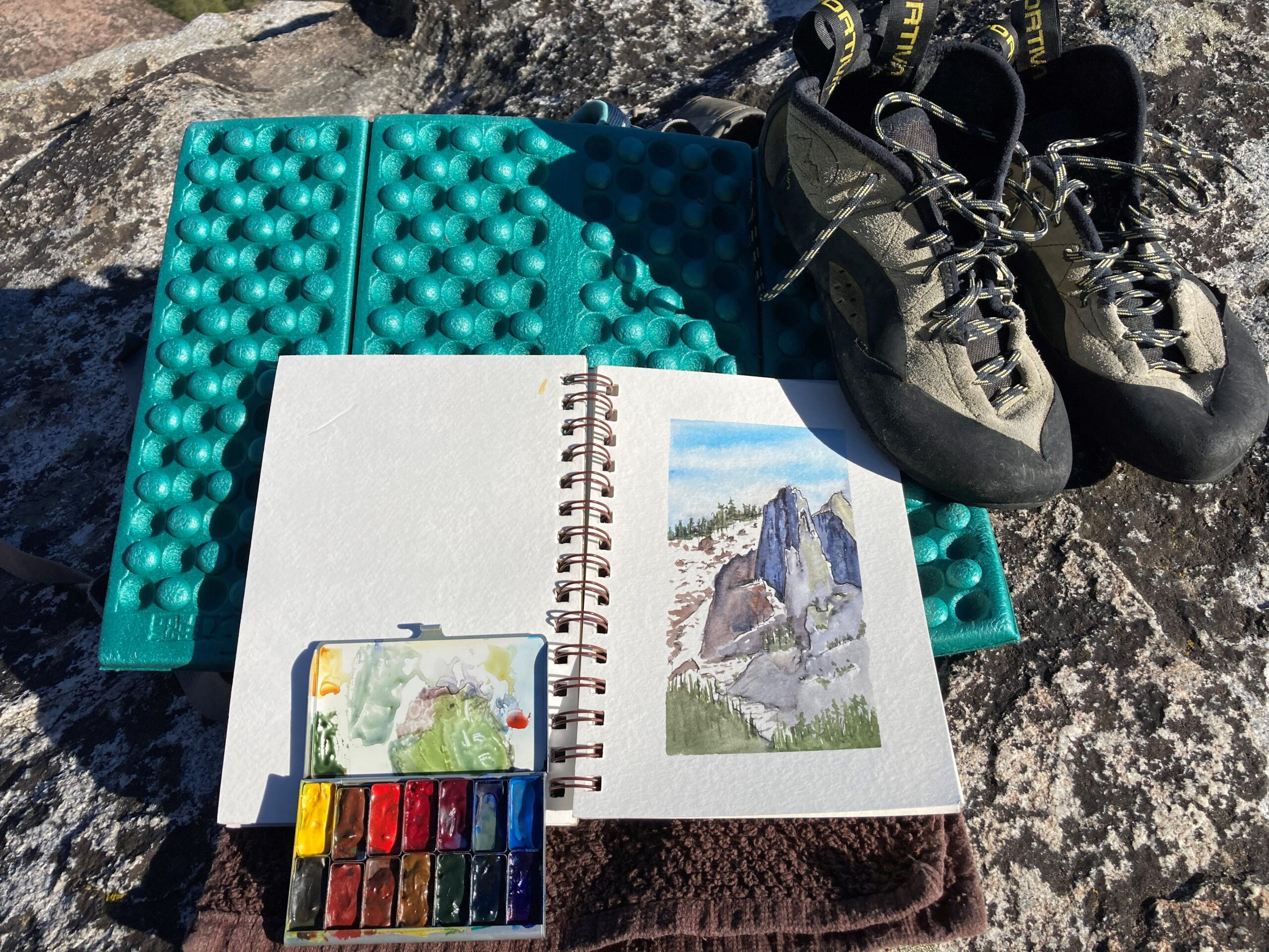 Photo showing a small watercolor kit with multiple paint colors, a sketchbook open to a watercolor painting of a mountain scene, and a pair of hiking boots, all resting on a folded sleeping pad.