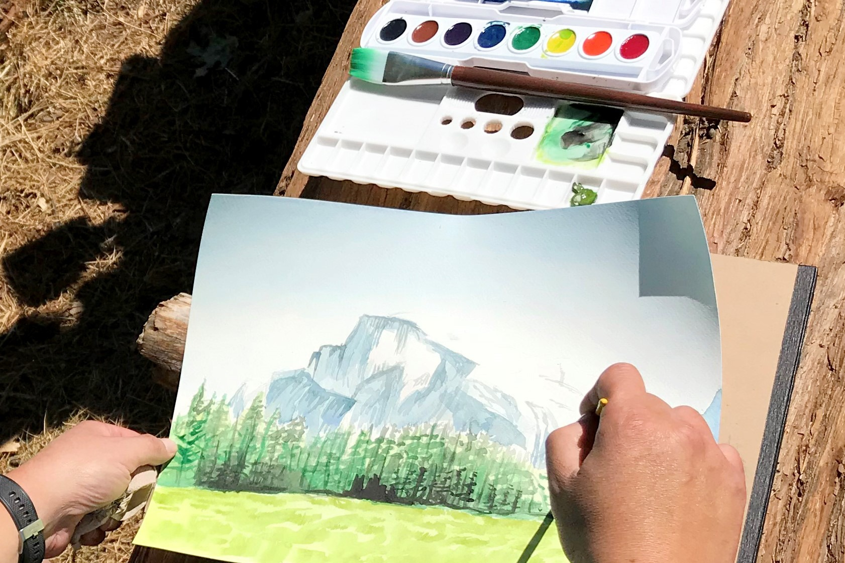 Photo showing an art class student's hands holding an in-progress watercolor painting of Half Dome. A watercolor kit and paintbrush rest on a log beneath the painting.