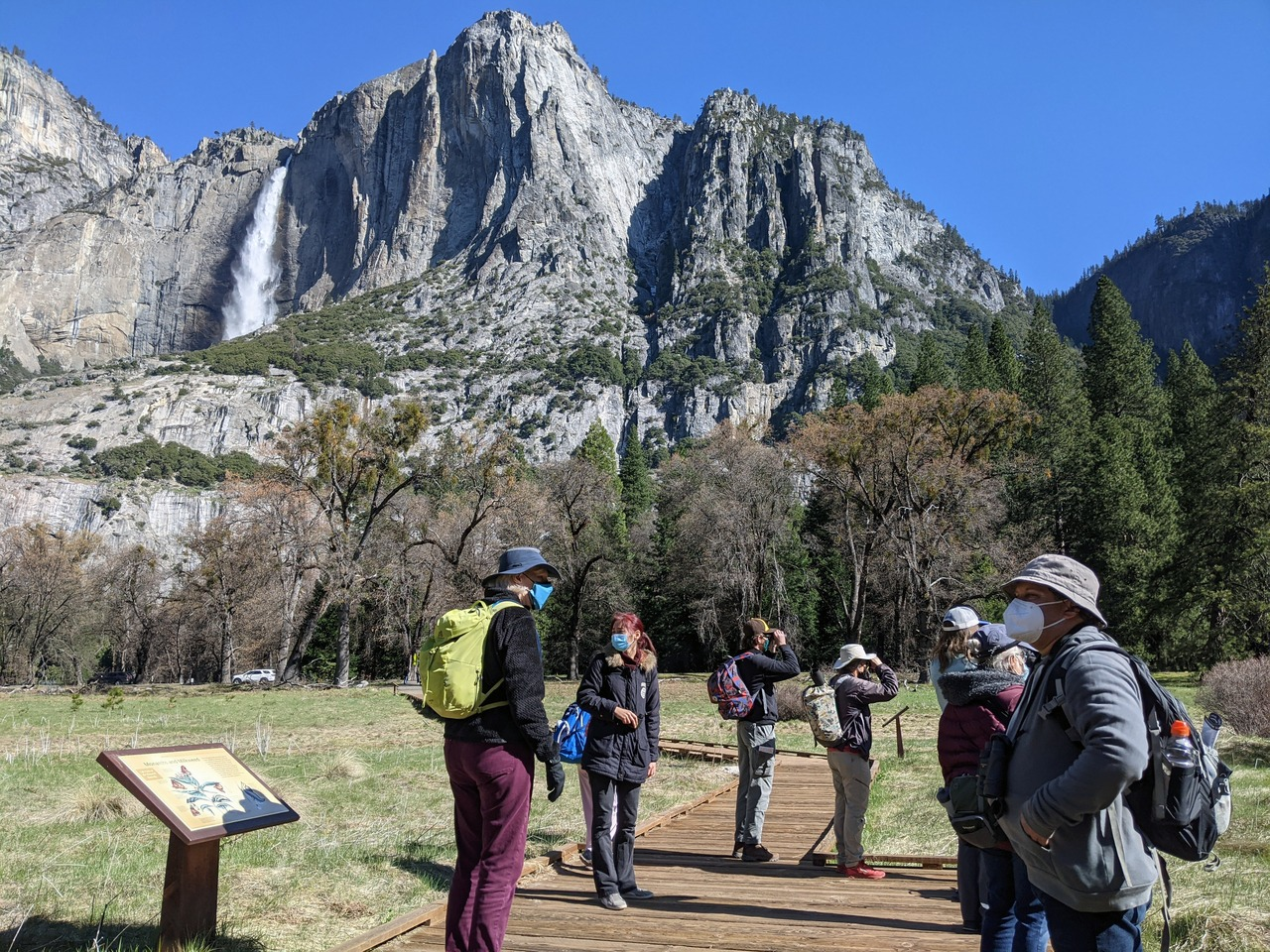 A group of people wearing face masks on a boardwalk in Yosemite Valley. A waterfall (Upper Yosemite Fall) flows in the background.