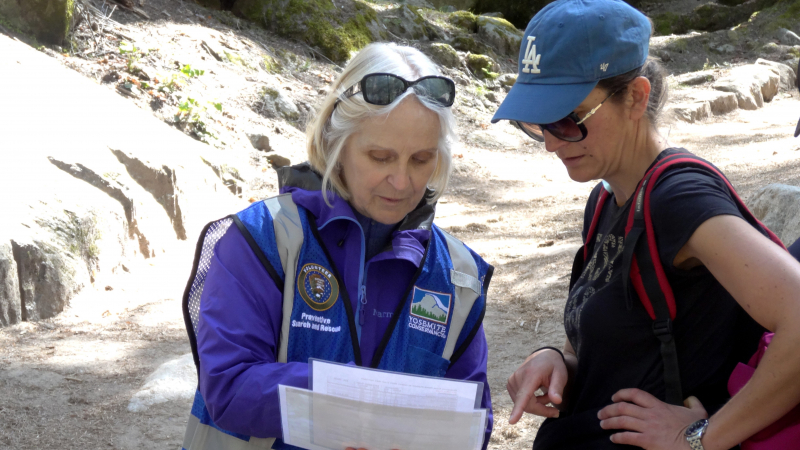 A Yosemite Conservancy volunteer shares information with a hiker during a May 2019 Preventive Search and Rescue training day near the John Muir/Mist trailhead. Photo: Yosemite Conservancy/Mark Marschall.