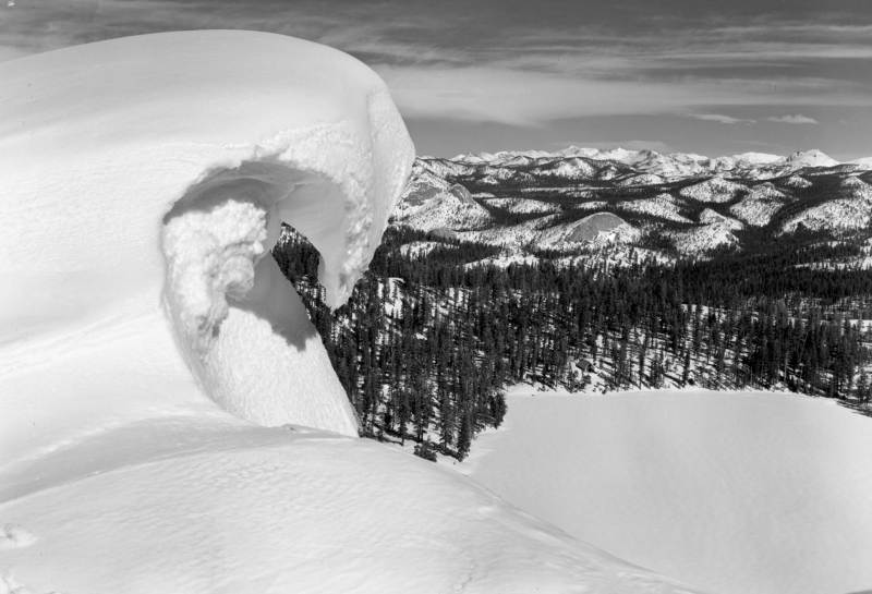 Snow cornices form when wind-blown snow builds up sideways and juts out over ridges or summits, creating dangerous unstable ledges. (Undated archival photo, courtesy of NPS)