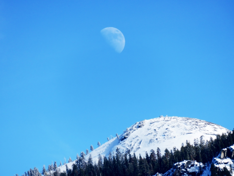 A snow-covered Yosemite dome mirrors the curve of a faint winter moon. Photo: Carolyn Botell.